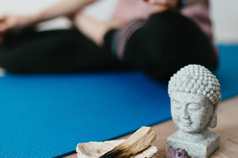 Woman Meditating with Buddha Statue