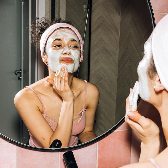 model applying moisturiser to face