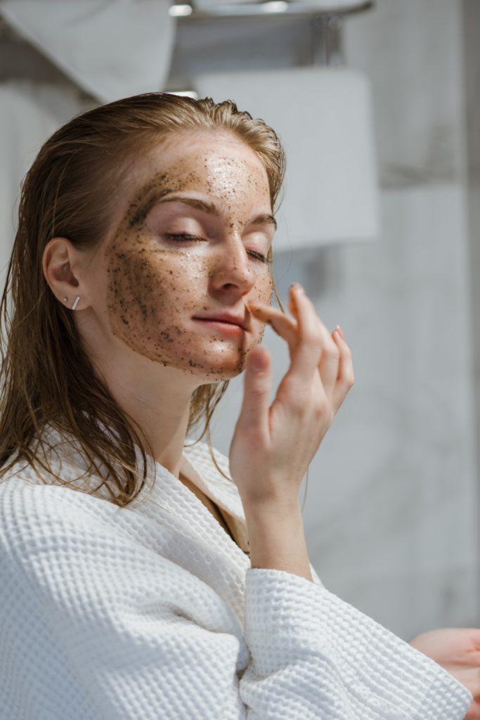 woman applying a coffee scrub face mask