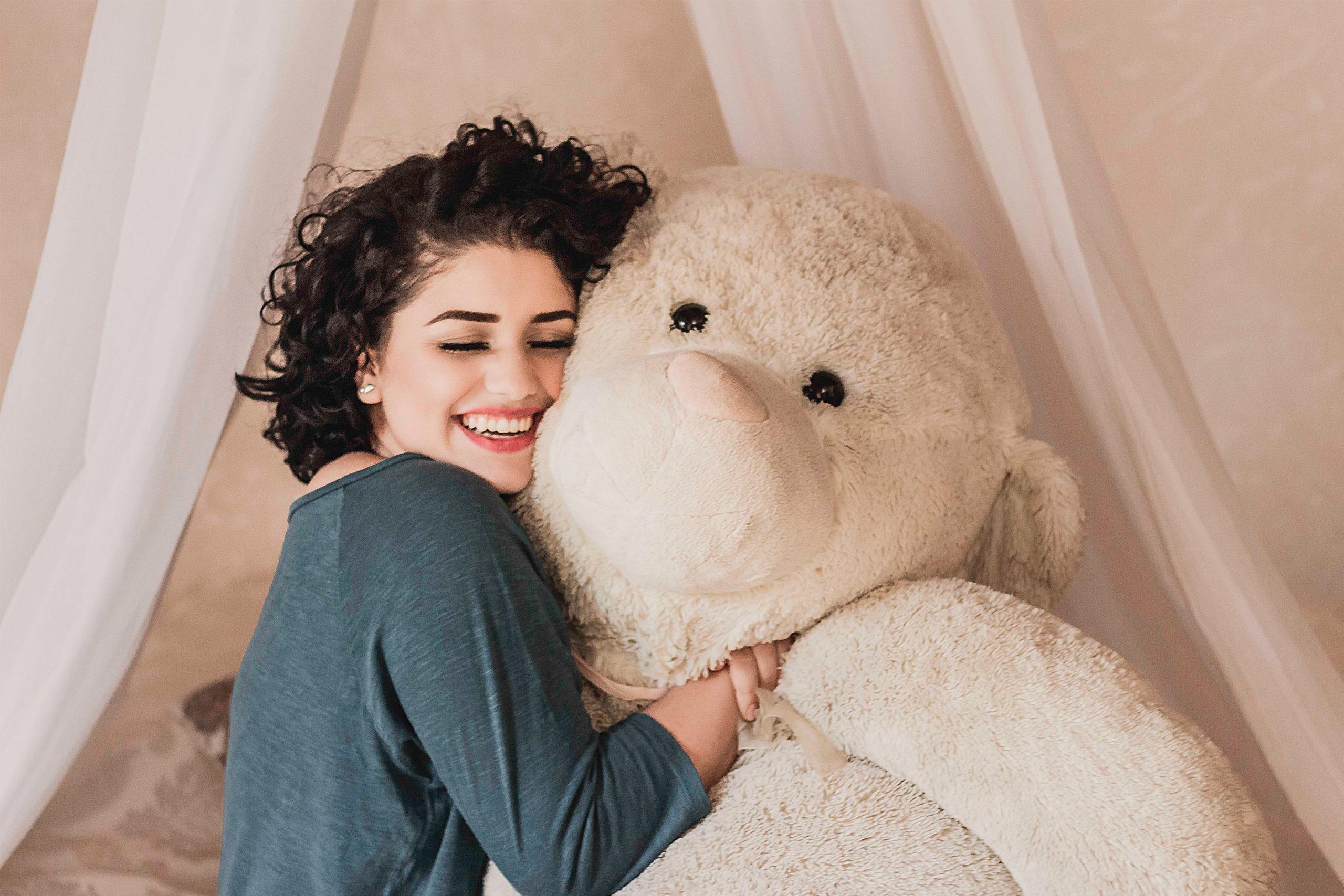 a woman hugging a giant teddy